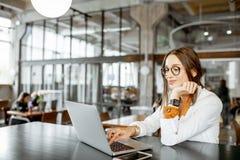 Empresaria joven con el ordenador portátil en la barra o la oficina fotos de archivo