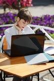 Mujer de negocios que usa el ordenador portátil en el café de la acera Foto de archivo libre de regalías