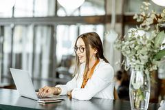 Empresaria joven con el ordenador port?til en la barra o la oficina fotos de archivo libres de regalías