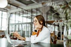 Empresaria joven con el ordenador port?til en la barra o la oficina imagen de archivo