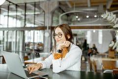 Empresaria joven con el ordenador port?til en la barra o la oficina imagen de archivo libre de regalías