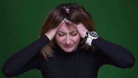Empresaria joven con el pelo de la castaña que comprime su cabeza que tiene un dolor de cabeza terrible en fondo verde almacen de video
