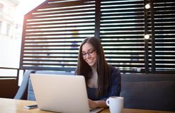 Empresaria joven con el teclado hermoso en el ordenador portátil, sentada de la sonrisa en cafetería Fotos de archivo