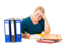 Empresaria joven con exceso de trabajo en el escritorio en blanco Fotos de archivo libres de regalías