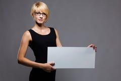 Empresaria joven con la tarjeta en blanco. Copyspace Foto de archivo libre de regalías