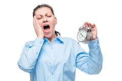 Empresaria joven con un despertador que bosteza en un blanco foto de archivo libre de regalías