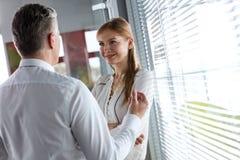 Empresaria joven confiada que escucha el hombre de negocios mientras que hace una pausa la ventana en oficina Foto de archivo libre de regalías