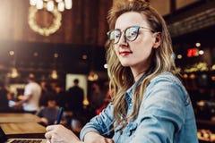 Empresaria joven del retrato en los vidrios de moda, sentándose en café delante del ordenador y tomando notas en cuaderno imagen de archivo libre de regalías