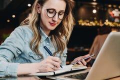 Empresaria joven del retrato en los vidrios de moda, sentándose en café delante del ordenador y tomando notas en cuaderno fotografía de archivo libre de regalías