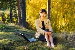 Empresaria joven en el bosque. Imagen de archivo libre de regalías
