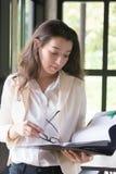 Empresaria joven en el papel del lugar de trabajo y de la lectura en oficina traje que lleva de la mujer de negocios que lleva a  fotos de archivo libres de regalías