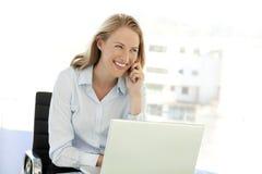 Empresaria joven en el teléfono en el lugar de trabajo Imagen de archivo libre de regalías