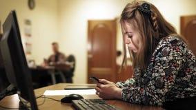 Empresaria joven en su escritorio y su compañero de trabajo en la parte posterior, golpeando ligeramente en el teléfono en la ofi almacen de metraje de vídeo