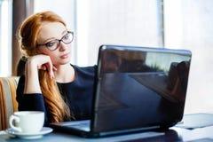 Empresaria joven en un descanso para tomar café Usando la computadora portátil Fotografía de archivo libre de regalías