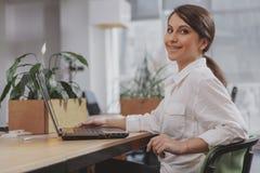 Empresaria joven encantadora que trabaja en su oficina fotos de archivo libres de regalías