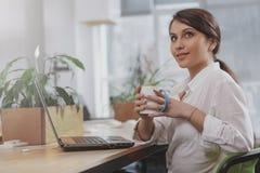 Empresaria joven encantadora que trabaja en su oficina imagen de archivo libre de regalías
