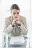Empresaria joven enfocada que se sienta en su escritorio que lee sus notas Imagenes de archivo