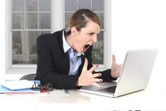 Empresaria joven enojada en la tensión en la oficina que trabaja en el ordenador Imagen de archivo