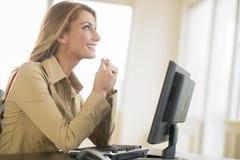 Empresaria joven feliz Looking Up While que se sienta en el escritorio Imagen de archivo