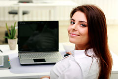 Empresaria joven feliz que se sienta en la tabla en su lugar de trabajo fotos de archivo libres de regalías