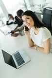 Empresaria joven feliz y hermosa que se sienta en una etiqueta de la oficina Imagen de archivo