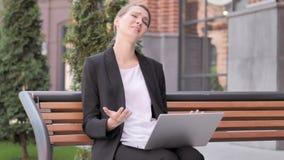 Empresaria joven Frustrated por el fracaso, sentándose en banco almacen de metraje de vídeo