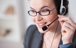 Empresaria joven hermosa con los auriculares en oficina Imagen de archivo libre de regalías