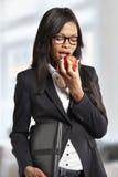 Empresaria joven hermosa que come la manzana imagenes de archivo