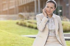 Empresaria joven hermosa que conversa en el teléfono móvil mientras que mira lejos Fotos de archivo