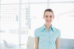 Empresaria joven hermosa que presenta en su oficina Imagen de archivo