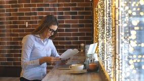 Empresaria joven hermosa que trabaja en un café y que estudia documentos almacen de video