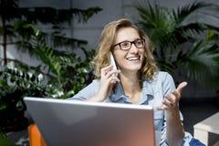 Empresaria joven hermosa que usa el teléfono móvil mientras que trabaja en el ordenador portátil Imágenes de archivo libres de regalías