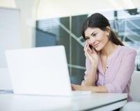 Empresaria joven hermosa que usa el teléfono móvil mientras que mira el ordenador portátil en oficina Fotografía de archivo libre de regalías