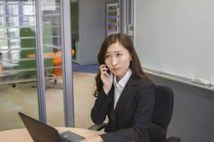 Empresaria joven infeliz que habla con un teléfono móvil Fotografía de archivo