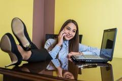 Empresaria joven linda que se sienta en una silla con sus pies en la tabla en la oficina Ella es sonriente y que habla en el telé foto de archivo