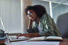 Empresaria joven preocupante que usa el ordenador portátil en el escritorio de oficina fotos de archivo libres de regalías