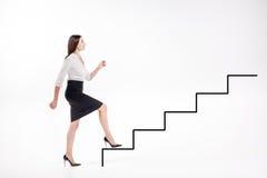 Empresaria joven que camina para arriba en las escaleras Fotos de archivo libres de regalías