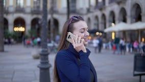 Empresaria joven que camina a través del cuadrado y que habla en el teléfono almacen de video