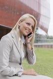 Empresaria joven que conversa en el teléfono móvil contra el edificio de oficinas Fotografía de archivo libre de regalías