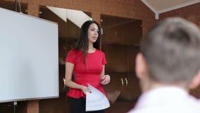 Empresaria joven que da la presentación a los colegas en sala de juntas almacen de video