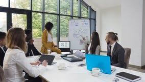 Empresaria joven que da la presentación a los hombres de negocios diversos en el encuentro, presentando nuevo proyecto a multi-ét almacen de video
