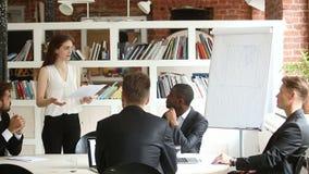 Empresaria joven que da la presentación a los hombres de negocios diversos en sala de reunión metrajes