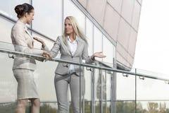 Empresaria joven que discute con el colega femenino en el balcón de la oficina Imágenes de archivo libres de regalías