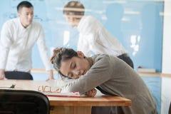 Empresaria joven que duerme durante la reunión fotografía de archivo