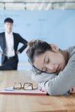 Empresaria joven que duerme durante la reunión, Boss decepcionado que la mira imágenes de archivo libres de regalías