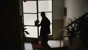 Empresaria joven que entra al apartamento con la maleta La hembra abre la puerta y la subida en las escaleras almacen de video
