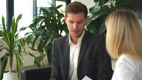 Empresaria joven que habla con un colega sobre el plan empresarial metrajes