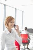 Empresaria joven que habla en el teléfono celular con los colegas en fondo en la oficina imágenes de archivo libres de regalías