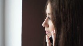 Empresaria joven que habla en el teléfono móvil en vestíbulo de la oficina almacen de metraje de vídeo