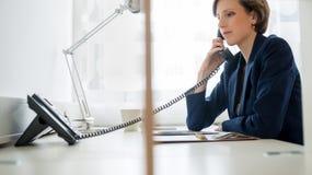 Empresaria joven que hace llamada de teléfono fotografía de archivo